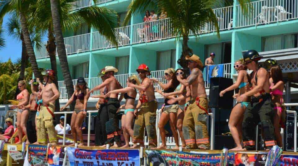 Firemen dancing with partgoers on a stage at the Lani Kai