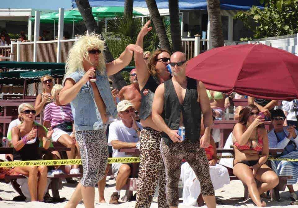 Men in glam rock costumes and leopard print trousers on the beach